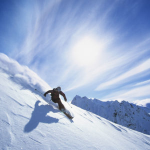 Skiing or snowboarding in the mountains.