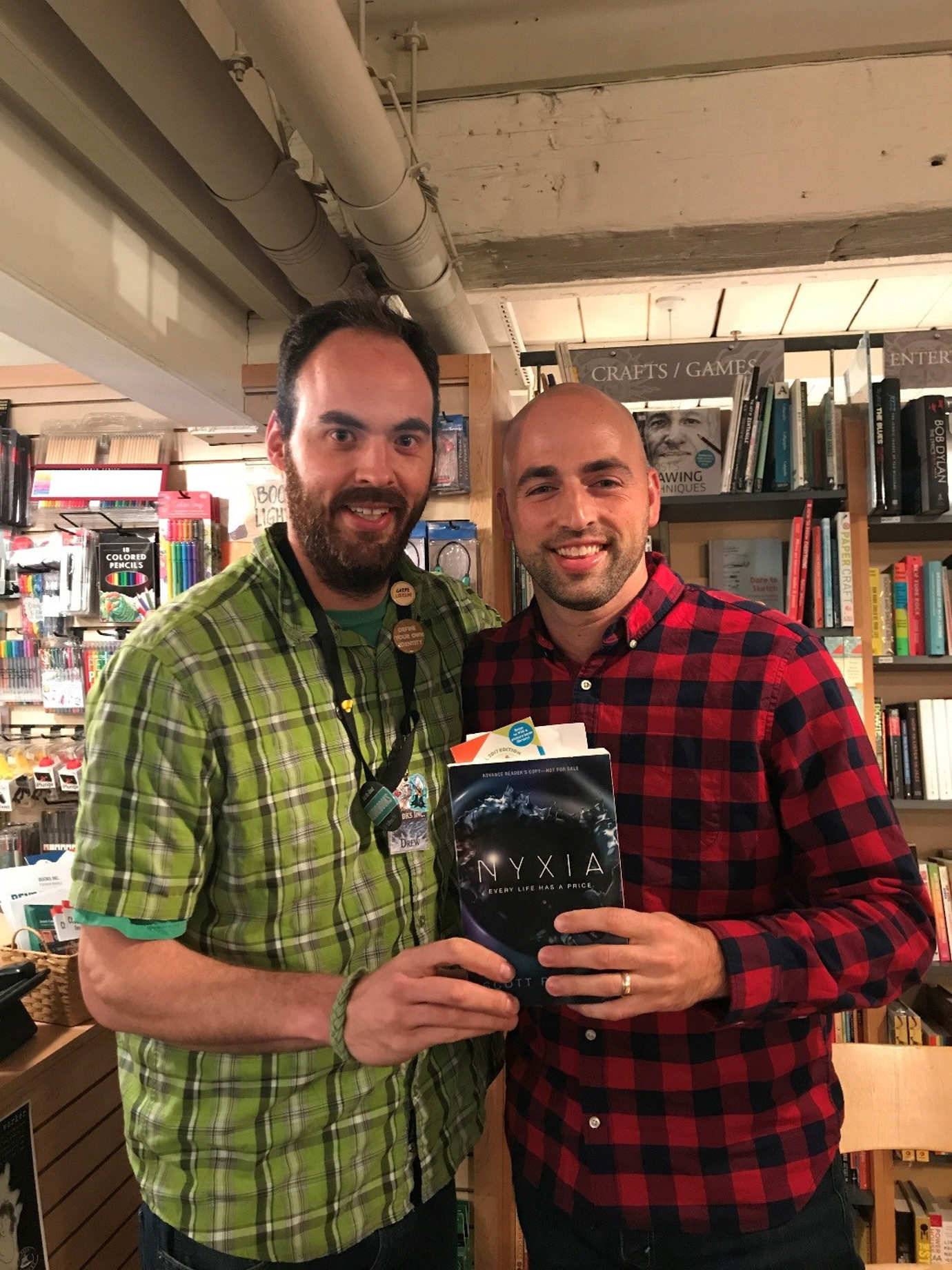 Books Inc. bookseller Drew poses with Scott Reintgen in celebration of <em>Nyxia</em> at our store in Palo Alto.
